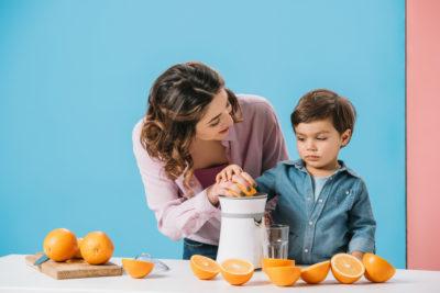 seorang ibu dan seorang anak laki-laki mengekstraksi jus jeruk