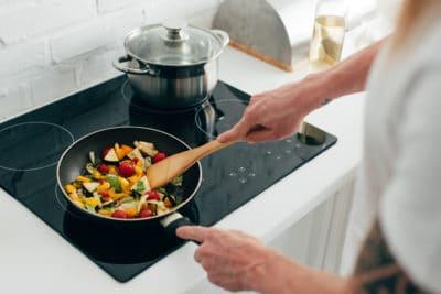 pria sedang menumis sayur-sayuran