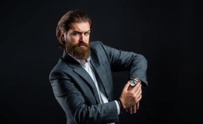 pria memegang jam tangannya